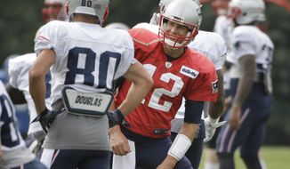 New England Patriots quarterback Tom Brady (12), center right, speaks with wide receiver Danny Amendola (80) while warming up with teammates at NFL football training camp, Thursday, Aug. 3, 2017, in Foxborough, Mass. Brady turned 40-years-old Thursday. (AP Photo/Steven Senne)
