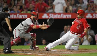 Los Angeles Angels' Albert Pujols, right, scores as Philadelphia Phillies catcher Cameron Rupp takes a late throw during the third inning of a baseball game, Wednesday, Aug. 2, 2017, in Anaheim, Calif. (AP Photo/Mark J. Terrill)