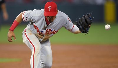 Philadelphia Phillies second baseman Cesar Hernandez can't handle a ball hit by Los Angeles Angels' Ben Revere during the third inning of a baseball game, Wednesday, Aug. 2, 2017, in Anaheim, Calif. Hernandez was charged with an error on the play. Revere was safe at first, and a run scored. (AP Photo/Mark J. Terrill)