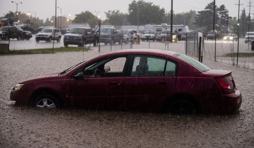 In this Wednesday, Aug. 2, 2017 photo, a car sits idle as rain water stalled it out at the border of Flint and Burton, Mich. The storms Wednesday evening brought several inches of rain in places. (Jake May/The Flint Journal-MLive.com via AP)