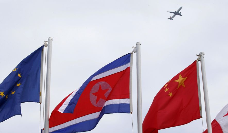A North Korean flag flies with other flags of the ASEAN countries and its dialogue partners outside the Philippine International Convention Center, the venue for the Aug. 2-8, 2017 50th ASEAN Foreign Ministers' Meeting, as a passenger plane flies above Thursday, Aug. 3, 2017 in Manila, Philippines. (AP Photo/Bullit Marquez)