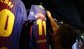 A man holds a FC Barcelona's Neymar t-shirt in a store of the Camp Nou stadium in Barcelona, Spain, Wednesday, Aug. 2, 2017. Neymar has told Barcelona that he plans to leave the club, with a blockbuster move to Paris Saint-Germain seemingly imminent. (AP Photo/Manu Fernandez)