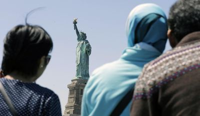 "FILE - In this May 7, 2015, file photo, people look at the Statue of Liberty from a ferry boat in Jersey City, N.J. Senior White House aide Stephen Miller told reporters Wednesday, Aug. 2, 2017, that the poem written by Emma Lazarus about the ""huddled masses"" is not part of the original Statue of Liberty. Miller says the Statue of Liberty is a ""symbol of American liberty lighting the world"" and suggested the statue had little to do with immigrants. The National Park Services says Lazarus' sonnet depicts the statue as a symbol of immigration and opportunity. (AP Photo/Mel Evans, File)"