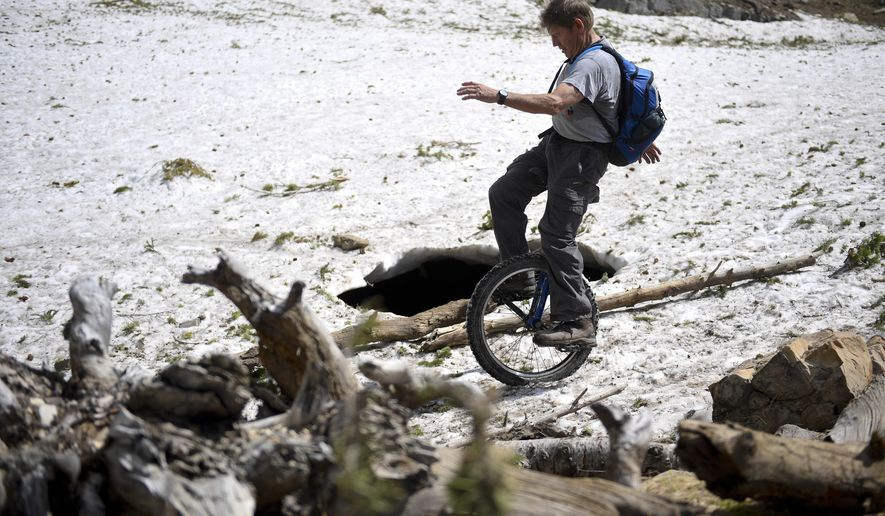 In this Thursday, July 13, 2017 photo, Guy Hansen rides his mountain unicycle through a patch of snow along Mount Timpanogos Trail in American Fork Canyon near Provo, Utah. (Isaac Hale/The Daily Herald via AP)