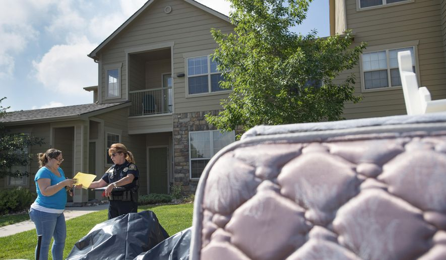 ADVANCE FOR USE SATURDAY, AUG 5 - In this Thursday, July 27, 2017 photo, Larimer County, Colo., Sheriff's Department deputy Barb Bowman hands paperwork to a homeowner after a tenant was evicted from a condominium in south Fort Collins, Colo. (Austin Humphreys/The Coloradoan via AP)