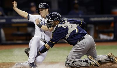 Milwaukee Brewers catcher Manny Pina, right, tags out Tampa Bay Rays' Corey Dickerson at home plate as Dickerson tried to score on a double by Evan Longoria during the seventh inning of a baseball game Friday, Aug. 4, 2017, in St. Petersburg, Fla. (AP Photo/Chris O'Meara)