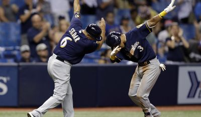 Milwaukee Brewers' Orlando Arcia (3) celebrates with third base coach Ed Sedar (6) after Arcia hit a home run off Tampa Bay Rays relief pitcher Sergio Romo during the eighth inning of a baseball game Friday, Aug. 4, 2017, in St. Petersburg, Fla. (AP Photo/Chris O'Meara)