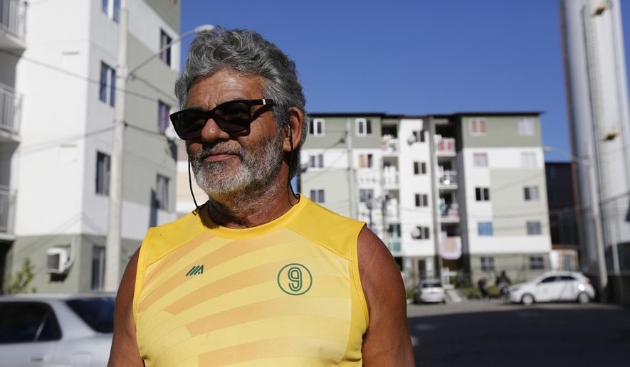 In this July 20, 2017, photo, Jorge Ramos stands in front of the Parque Carioca social housing complex in Rio de Janeiro, Brazil. Ramos exchanged his old house for three 645-square-foot apartments. (AP Photo/Liliana Michelena)