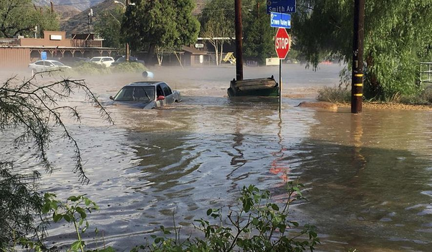 In this Thursday, Aug. 3, 2017 photo provided by @brandibrands shows a car submerged by water after a flash flood in Acton, Calif. The Southern California desert community is cleaning up on Friday, Aug. 4, 2017 after thunderstorms unleashed muddy torrents through streets, threatened a commuter rail line and forced the rescue of the trapped motorists. (@brandibrands via AP)