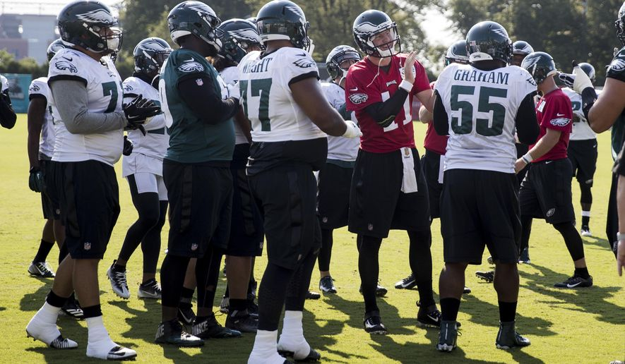 Philadelphia Eagles quarterback Carson Wentz (11) gathers with his teammates during an NFL football training camp in Philadelphia, Friday, Aug. 4, 2017. (AP Photo/Matt Rourke)