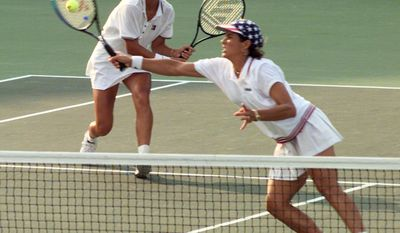 FILE - In this Aug. 3, 1996, file photo, America's doubles team of Mary Joe Fernandez, left, and Gigi Fernandez return to the Czech Republic's doubles team of Jana Novotna and Helena Sukova in the gold medal match at the Stone Mountain Tennis Center on Saturday Aug. 3, 1996, in Stone Mountain, Ga. Gigi Fernandez's prediction of taking the New York Empire to the World TeamTennis finals in her coaching debut nearly came true. The Empire lost a supertiebreaker in their last match of the season, just missing a spot in the WTT finals. Fernandez won U.S. Olympic gold in doubles with teammate Mary Joe Fernandez at the 1992 Barcelona and 1996 Atlanta Games. (AP Photo/Lynne Sladky, File)