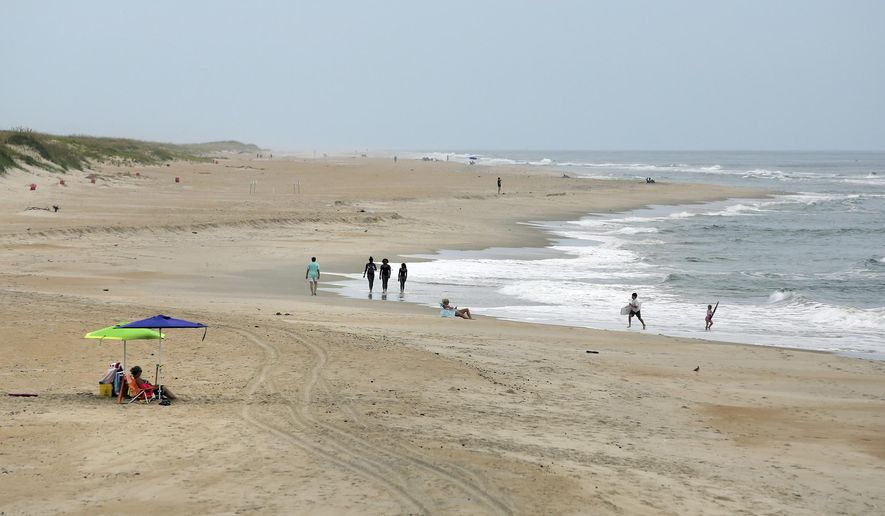 The beach in Avon, N.C., on Hatteras Island is nearly empty, Thursday, Aug. 3, 2017. Workers building the replacement Bonner Bridge over the Oregon Inlet accidentally severed two underground power lines on July 27, that led to the mandatory evacuation of vacationers at the height of the tourist season. Utility officials say they expect to restore power to two North Carolina islands by the weekend. (Steve Earley/The Virginian-Pilot via AP)