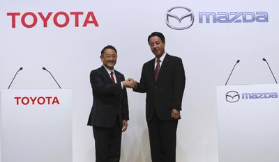 Toyota Motor Corp. President Akio Toyoda, left, and Mazda Motor Corp. President Masamichi Kogai, pose for media prior to a press conference in Tokyo Friday, Aug. 4, 2017.  Japanese automakers Toyota Motor Corp. and Mazda Motor Corp. said Friday they plan to spend $1.6 billion to set up a joint-venture auto manufacturing plant in the U.S. — a move that will create up to 4,000 jobs. (AP Photo/Eugene Hoshiko)