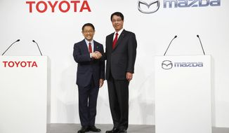 FILE - In this May 13, 2015 file photo, Toyota Motor Corp. President Akio Toyoda, left, and Mazda Motor Corp. President Masamichi Kogai pose for photographers prior to a press conference in Tokyo. Japanese automakers Toyota Motor Corp. and Mazda Motor Corp. are partnering in electric vehicles with a deal expected to be announced later Friday, Aug. 4, 2017. (AP Photo/Shizuo Kambayashi, File)