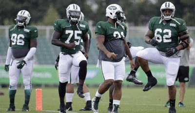 New York Jets defensive lineman Devon Still, far right, works out with teammates during NFL football training camp, Friday, Aug. 4, 2017, in Florham Park, N.J. (AP Photo/Julio Cortez)