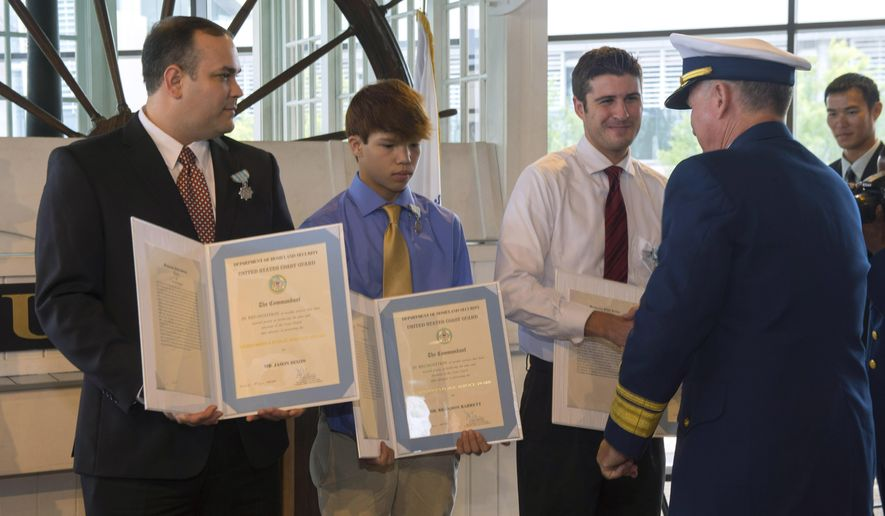 From left, U.S. Coast Guard Meritorius Public Service Medal citations are held by Jason Dixon, Brandon Barrett,14, and Robbie Reynold, after they were presented medals for their service by U.S. Coast Guard Rear Admiral Dave Callahan, Commander of the USCG Eighth District headquartered in New Orleans, on Friday, Aug. 4, 2017 in Baton Rouge, La.  The Coast Guard awarded the medals to the four people for rescuing a woman and her dog from a sinking car during historic flooding in Louisiana last summer, a dramatic scene captured on video.  ( Travis Spradling/The Advocate via AP)