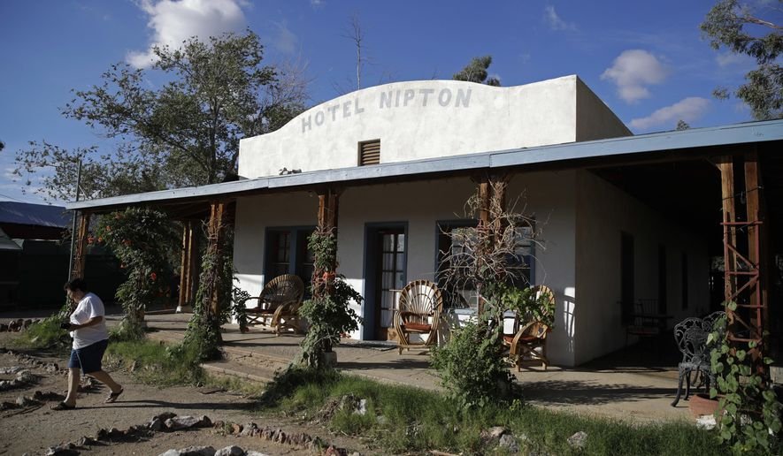 A woman walks out of the Hotel Nipton, Thursday, Aug. 3, 2017, in Nipton, Calif. American Green Inc., one of the nation's largest cannabis companies, announced it has bought the entire 80 acre California desert town of Nipton. (AP Photo/John Locher)