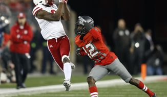 FILE - In this Saturday, Nov. 5, 2016 file photo, Nebraska receiver Stanley Morgan tries to make a catch against Ohio State defender Denzel Ward during an NCAA college football game in Columbus, Ohio. Nebraska receiver Stanley Morgan Jr. knows everything he does on and off the football field will be scrutinized a little more this season following his run-in with the law last spring. Morgan and teammate Antonio Reed were charged with misdemeanor marijuana possession following a traffic stop in Port Orange, Florida, in May.  (AP Photo/Paul Vernon, File)