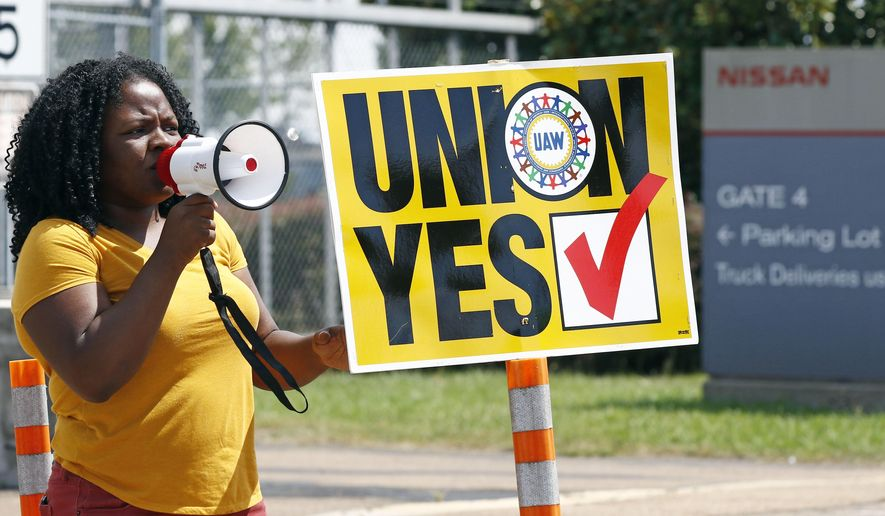 A UAW supporter uses a bull horn to remind eligible workers to vote for the union while standing outside an employee vehicle entrance at the Nissan vehicle assembly plant in Canton, Miss., Friday, Aug. 4, 2017. Union members set up informational lines outside employee entrances at the plant and greeted all shifts of workers arriving and leaving, reminding workers to vote for the union. The vote for union representation of line workers concludes Friday evening. (AP Photo/Rogelio V. Solis)