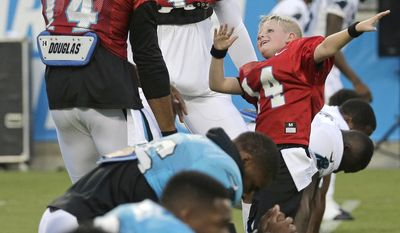 "Carolina Panthers' Cam Newton (1) and Joe Webb (14) dance with Domanic ""Dom"" Fuller, right, during practice at the NFL football team's Fan Fest in Charlotte, N.C., Friday, Aug. 4, 2017. Fuller was signed to a one-day contract with the team through Make-A-Wish. (AP Photo/Chuck Burton)"