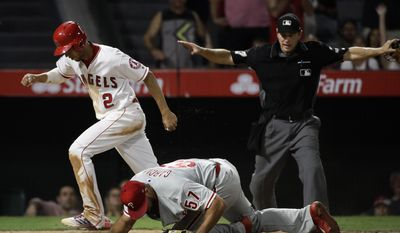 Los Angeles Angels' Andrelton Simmons, left, is called safe by home plate umpire Ben May after he scored on a wild pitch by Philadelphia Phillies relief pitcher Luis Garcia, bottom, during the eighth inning of a baseball game, Thursday, Aug. 3, 2017, in Anaheim, Calif. (AP Photo/Jae C. Hong)