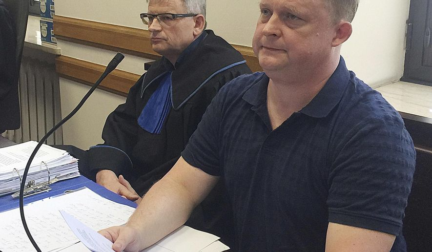 FILE - This file photo from June 21, 2017, shows Tomasz Piatek, right, a journalist for the Polish newspaper Gazeta Wyborcza, sits alongside his lawyer in a court in Warsaw, Poland. The international security organization OSCE urged Thursday that the Polish government show restraint as it pursues a legal case against Piatek, who alleges in a new book that the defense minister has shady ties to Russia. The photo shows Piatek in court in a separate case in which he is being sued by an American political activist for defamation. (AP Photo/Vanessa Gera, file)