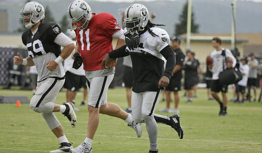 Oakland Raiders running back Marshawn Lynch, right, runs with long snapper Jon Condo, left, and kicker Sebastian Janikowski, center, during an NFL football training camp Friday, Aug. 4, 2017, in Napa, Calif. (AP Photo/Eric Risberg)