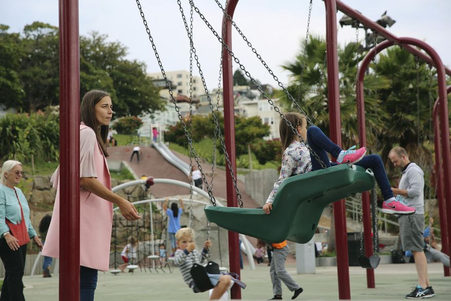 Parents enjoy a day at Dolores Park with their children at the popular San Francisco park on Friday, Aug. 4, 2017. The San Francisco park where three people were shot on a sunny Thursday afternoon underwent a $20 million renovation last year and immediately became one of the city's most popular destinations — and a magnet for drug use, gang activity and violence. (AP Photo/Linda Wang)