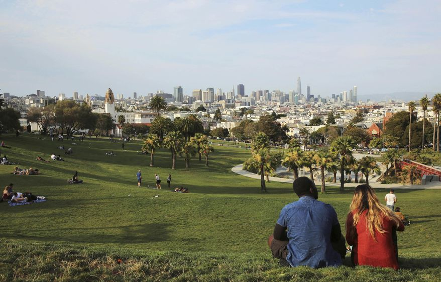 People enjoy at Dolores Park hours after San Francisco Police responded to reports of a shooting at the park in San Francisco on Thursday, Aug. 3, 2017. At least one gunman opened fire Thursday at the popular San Francisco park packed with families and tourists, leaving a few people wounded and sending dozens of panicked people running for cover, witnesses and police said. (AP Photo/Linda Wang)
