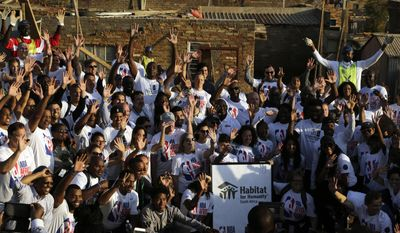 NBA staff, players and their families members, pose for a group photograph after helping out in building houses in Lenasia South of Johannesburg, South Africa, Thursday, Aug. 3, 2017. As part of the NBA Africa Game, and Habitat for Humanity South Africa, 200 volunteers from the NBA players, families and executives help build 10 homes. (AP Photo/Themba Hadebe)