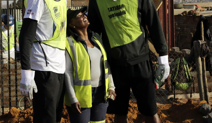 Rondae Hollis-Jefferson of Brooklyn Nets, left, and Kemba Walker of Charlotte Hornets pose for a photograph with a local volunteer whilst helping in building a house in Lenasia, south of Johannesburg, South Africa, Thursday, Aug. 3, 2017. As part of the NBA Africa Game, and Habitat for Humanity South Africa, 200 volunteers from the NBA players, families and executives help build 10 homes. (AP Photo/Themba Hadebe)