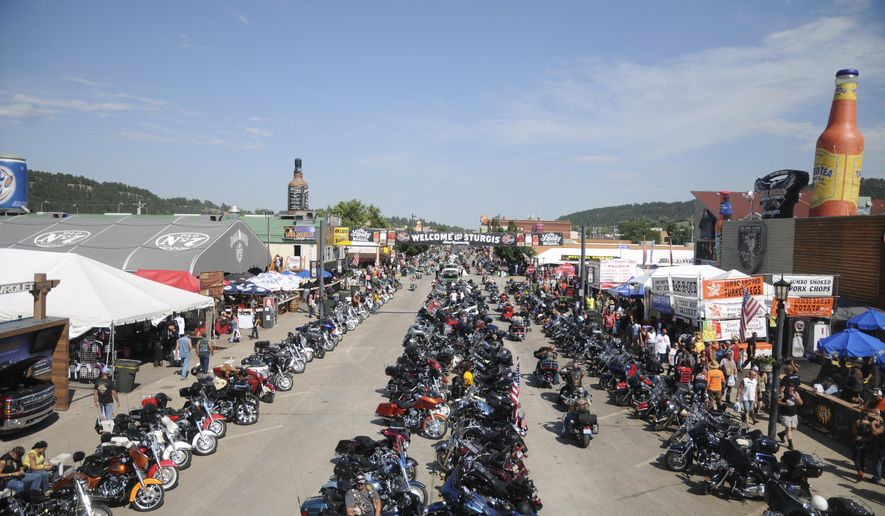 FILE - In this Aug. 5, 2015, file photo, motorcycles stretch down Main Street in Sturgis, S.D., for the landmark Sturgis Motorcycle Rally. The annual rally begins it's 10-day run Friday, Aug. 4, 2017. State transportation officials are expecting between 500,000 and 600,000 bikers this year. (AP Photo/James Nord, File)