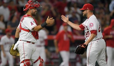 Los Angeles Angels' Juan Graterol, left, and relief pitcher Bud Norris congratulate each other after the Angels defeated the Oakland Athletics 8-6 in a baseball game, Friday, Aug. 4, 2017, in Anaheim, Calif. (AP Photo/Mark J. Terrill)