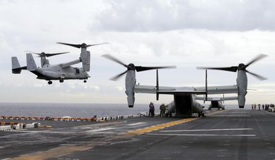 In this June 29, 2017, file photo U.S. Marine MV-22B Osprey aircraft land on the deck of the USS Bonhomme Richard amphibious assault ship off the coast from Sydney during events marking the start of Talisman Saber 2017, a biennial joint military exercise between the United States and Australia. A MV-22 Osprey that had launched from the USS Bonhomme was conducting regularly scheduled operations when it crashed into the water off Australia's east coast, Saturday, Aug. 5. (Jason Reed/Pool Photo via AP, File)