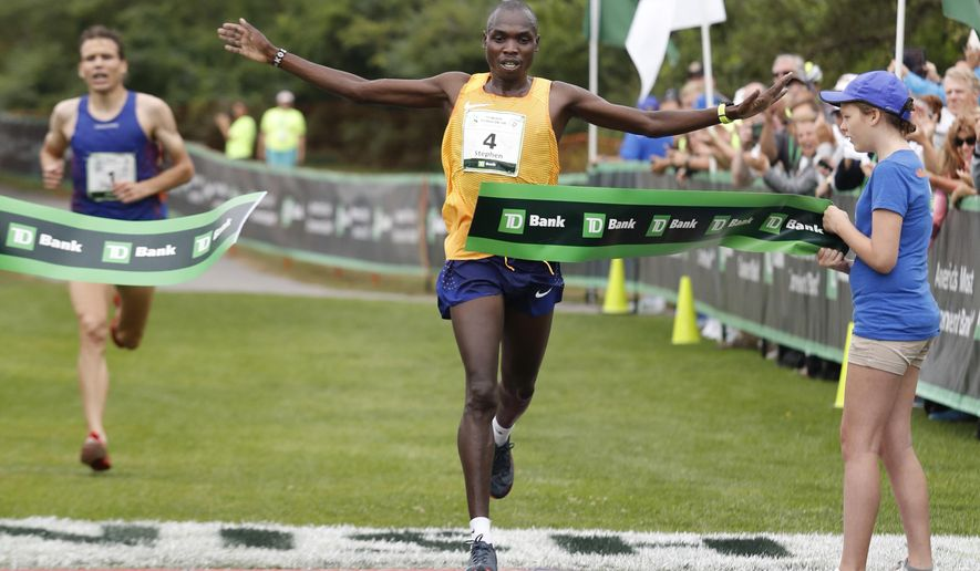 Stephen Kosgei-Kibet, 30, of Kenya, right, crosses the finish line ahead of defending champion Ben True, of Hanover, N.H., left, to win the men's division of the 20th annual TD Beach To Beacon 10K road race Saturday, Aug. 5, 2017 in Cape Elizabeth, Maine. (AP Photo/Joel Page)