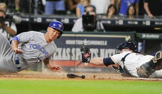 Toronto Blue Jays' Rob Refsnyder, left, slides past Houston Astros catcher Brian McCann to score the go-ahead run on Ryan Goins' single during the 10th inning of a baseball game, Saturday, Aug. 5, 2017, in Houston. (AP Photo/Eric Christian Smith)
