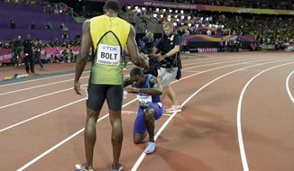 Gold medal winner United States' Justin Gatlin, centre, knees in front of Jamaica's Usain Bolt, left, who won bronze in the men's 100m final, during the World Athletics Championships in London Saturday, Aug. 5, 2017. (AP Photo/Matthias Schrader)