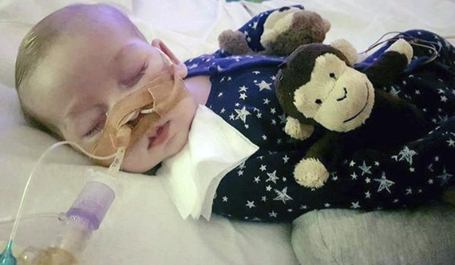 """FILE - In this undated file photo provided by his family,  Charlie Gard lays in Great Ormond Street Hospital in London. A member of the medical team that treated Charlie Gard has defended their care for the infant who died of a rare genetic disease while criticizing political and religious leaders who intervened in the case. The health care worker wrote an anonymous opinion piece in the Guardian newspaper Saturday, Aug. 5, 2017, saying staff at Great Ormond Street Hospital """"loved this child to bits"""" but reached the point where they could do no more. (Family of Charlie Gard via AP, File)"""