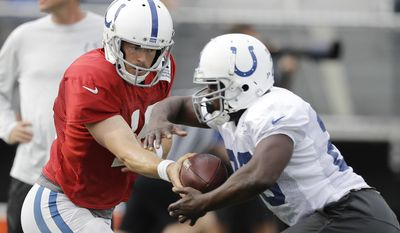 Indianapolis Colts quarterback Scott Tolzien (16) hands off to running back Frank Gore (23) during practice at the NFL football team's training camp Saturday, Aug. 5, 2017, in Indianapolis, (AP Photo/Darron Cummings)
