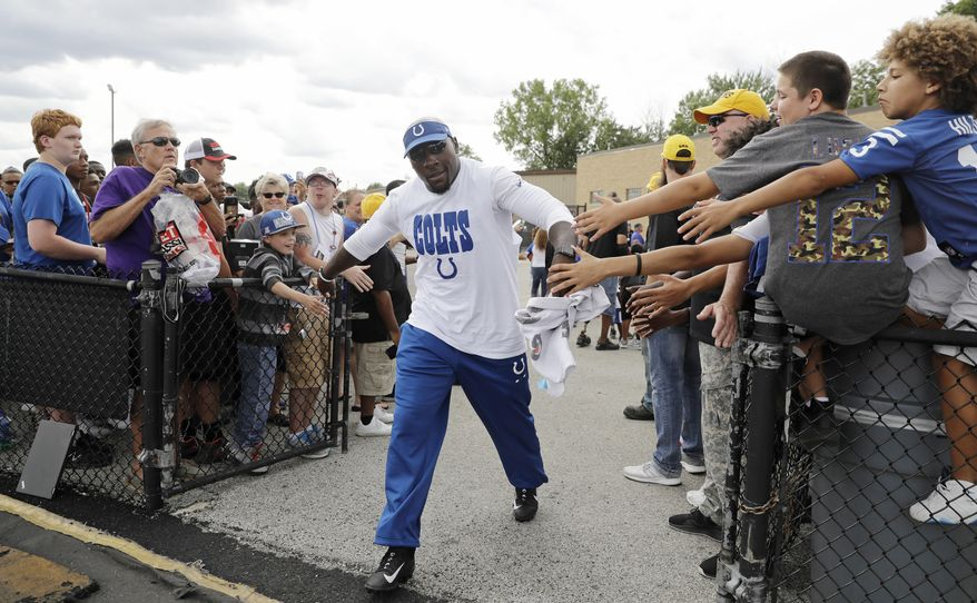 Former Indianapolis Colts player Robert Mathis greets fans as he walks out to a practice during the NFL football team's training camp Saturday, Aug. 5, 2017, in Indianapolis, (AP Photo/Darron Cummings)