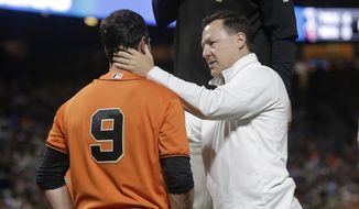 San Francisco Giants' Brandon Belt (9) is tended to by manager Bruce Bochy, top, and trainer Dave Groeschner after being hit by a pitch during the sixth inning of the team's baseball game against the Arizona Diamondback in San Francisco, Friday, Aug. 4, 2017. (AP Photo/Jeff Chiu)