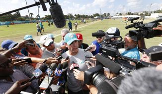 Miami Dolphins head coach Adam Gase, center, talks with members of the media after an NFL football training camp, Friday, Aug. 4, 2017, at the Dolphins training facility in Davie, Fla. (AP Photo/Wilfredo Lee)