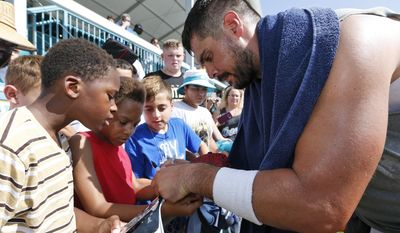 Miami Dolphins quarterback Matt Moore, right, signs autographs after an NFL football training camp, Friday, Aug. 4, 2017, at the Dolphins training facility in Davie, Fla. (AP Photo/Wilfredo Lee)