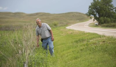 ADVANCED FOR RELEASE SATURDAY, AUGUST 5, 2017 Herpetologist Dennis Ferraro walks along a fence that helps steer turtles into a pipe so they can safely cross Highway 83 at the Valentine National Wildlife Refuge Tuesday, June 6, 2017, in Valentine, Neb. (Matt Dixon/The World-Herald via AP)