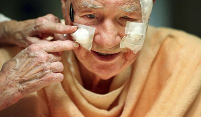 In this undated photo, with the help of his wife Marcia, John Dunlap receives his nightly leech treatment at his home in Memphis, Tenn. Marcia places several leeches on his face in an effort to increase pressure in his left eye. In conjunction with stem cell treatment, the Dunlaps hope that one day John may be a viable candidate for a procedure that could return some of his vision. (Jim Weber/The Commercial Appeal via AP)