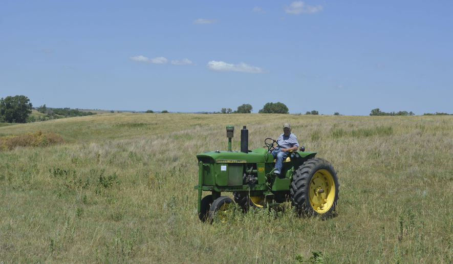 ADVANCE FOR SATURDAY AUG. 5 AND THEREAFTER - In a July 5, 2017 photo, James Wagner sits on his John Deere tractor in the rolling hills of his farm near Winnetoon, Neb. He planted in his pasture in 1967 a mixture of grasses native to Nebraska and says they are still going strong 50 years later. (Kelly Schnoor/The Norfolk Daily News via AP)