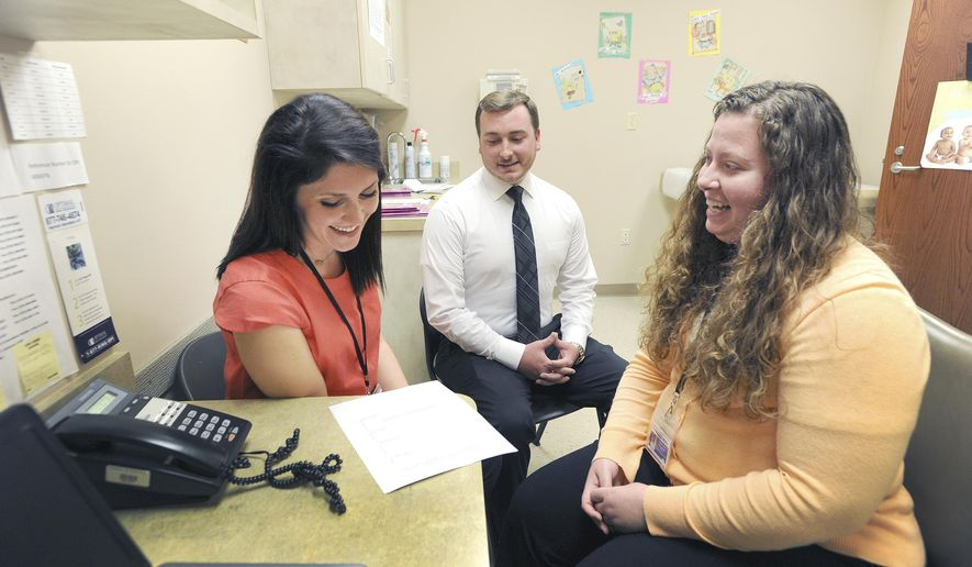 In this July 31, 2017, photo, Leah Lewis, left, and Brad Conrad, center, both WIC navigators, meet with Nutritionist Stephanie Johnson, right, as they go over WIC participation numbers inside the Green River District Health Department in Owensboro, Ky. (Alan Warren/The Messenger-Inquirer via AP)