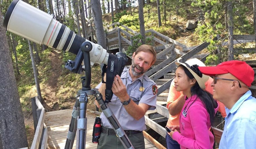 In this June 8, 2017 photo, Yellowstone National Park photographer Jim Peaco, left, gives Sunnyvale, Calif., tourists Amanda and Stephen Chou a lesson in shutter speeds while photographing harlequin ducks in the LeHardy Rapids section of the Yellowstone River in Yellowstone National Park, Wyo. From garbage truck driver to seasonal slide librarian in 1984, Peaco finally got a toehold on a dream job: Yellowstone National Park photographer.  (Brett French/The Billings Gazette via AP)