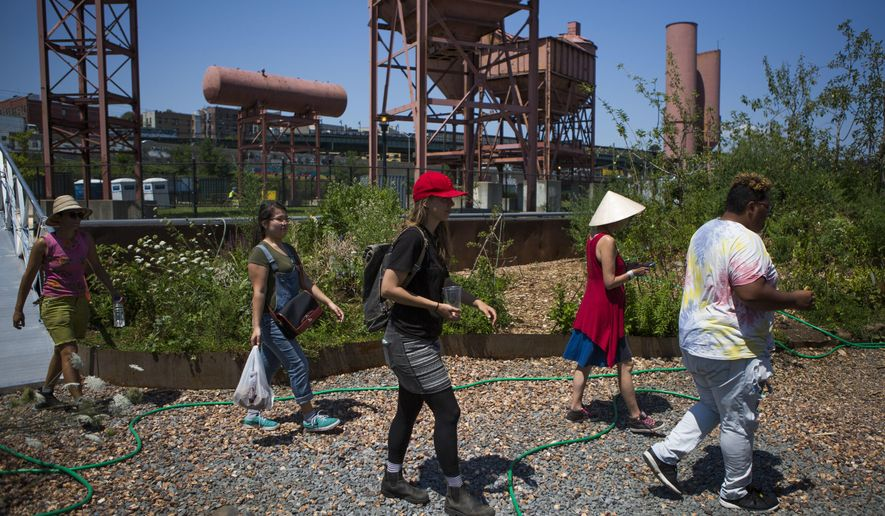 In this Aug. 1, 2017, photo, volunteers and crew arrive on the Swale in New York. The Swale garden is an old construction barge planted with vegetables, apple trees and fragrant herbs that gives New Yorkers a chance to pick their own dinners. (AP Photo/Michael Noble Jr.)