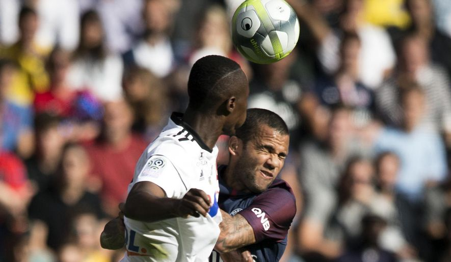 PSG's Dani Alves, right, and Amien's Khaled Adenon challenge for a header during the French League One soccer match between Paris Saint Germain and Amiens at the Parc des Princes stadium in Paris, France, Saturday, Aug. 5, 2017. (AP Photo/Kamil Zihnioglu)